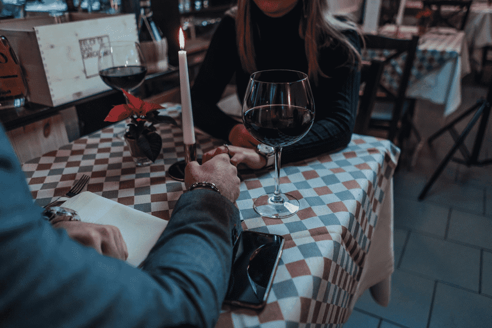 Elite professionals dating in a fancy restaurant while drinking wine