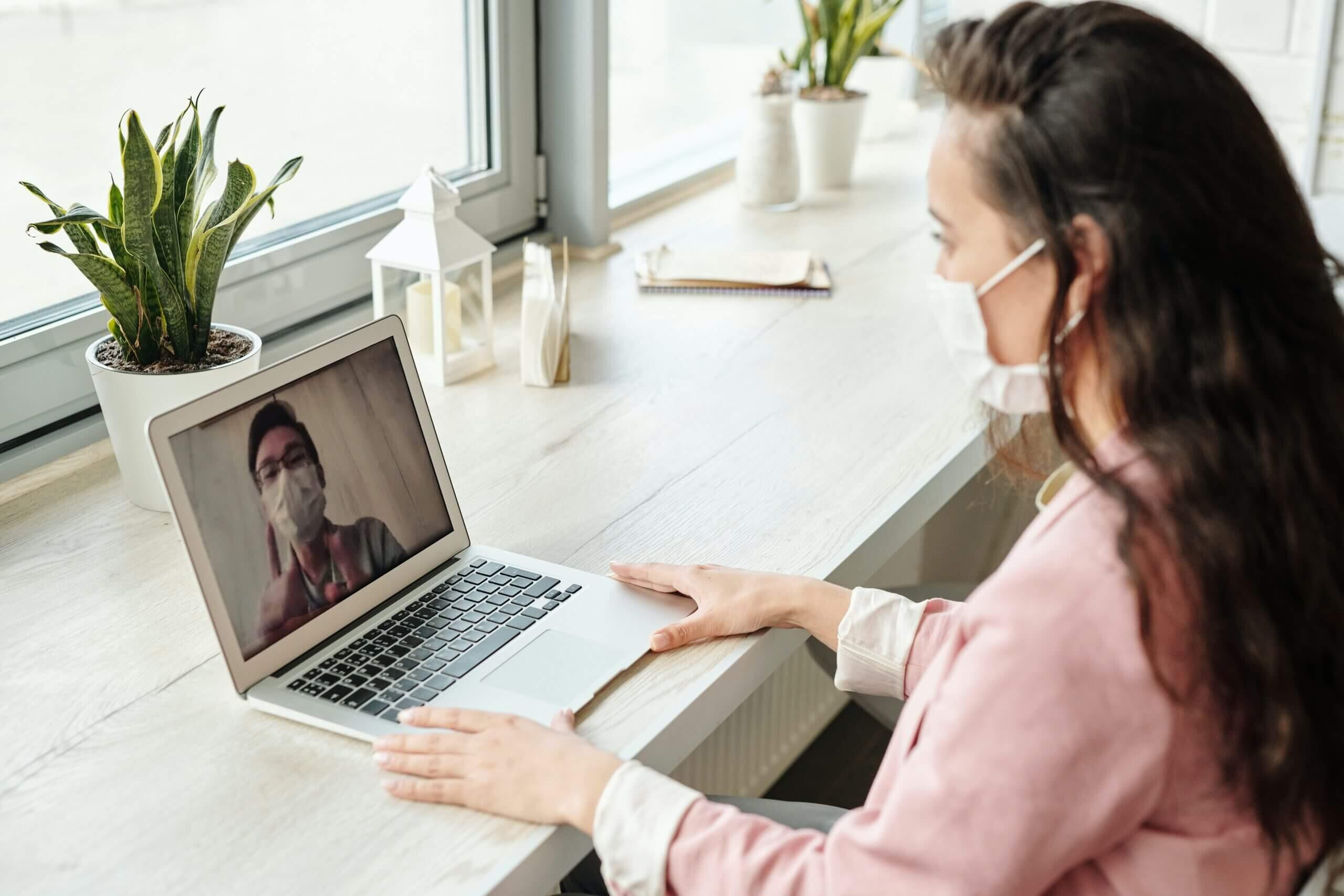 Girl with face mask talking to a guy using her laptop during quarantine