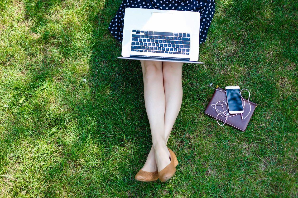 Single lady in polka dot dress sitting on the grass with a laptop on her lap