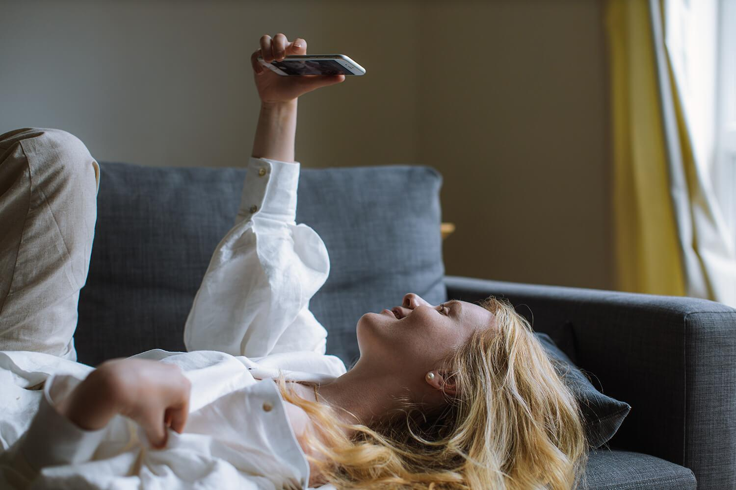 woman in white dress shirt holding a smartphone