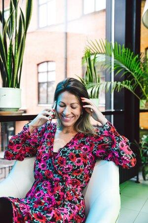 High-end single woman smiling while tallking to someone over the phone