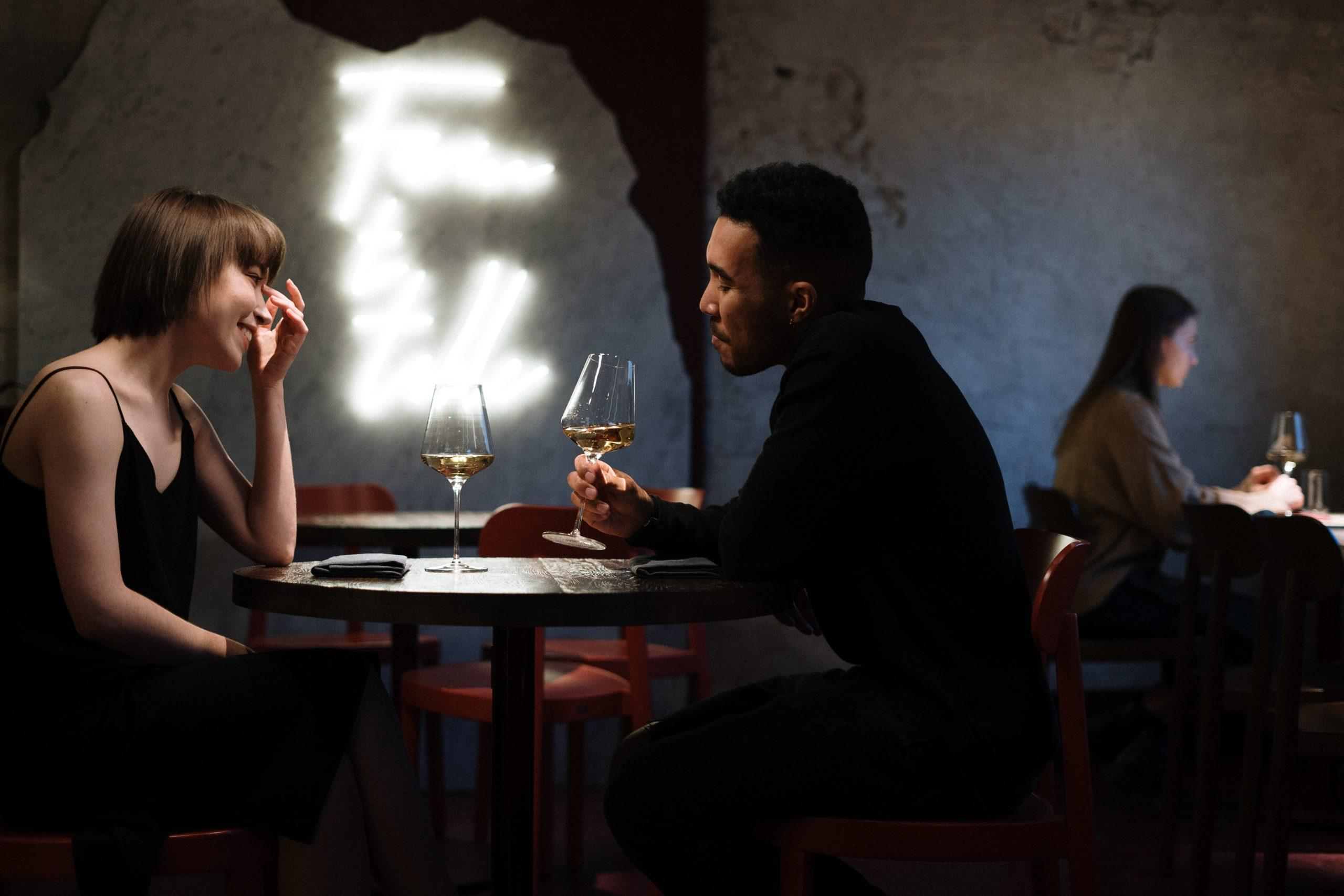Man in black long sleeved shirt and woman in black dress having wine in a fancy restaurant